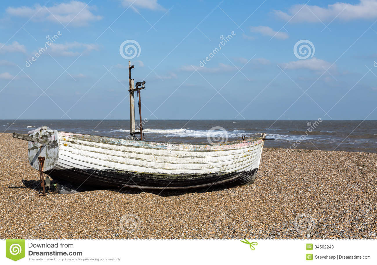 Ancient wooden painted fishing boat on pebble beach by North Sea in ...