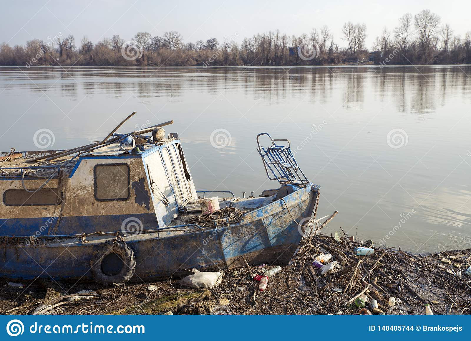 Old Fishing Boat Stuck In Trash On A Dirty Beach, Pollution