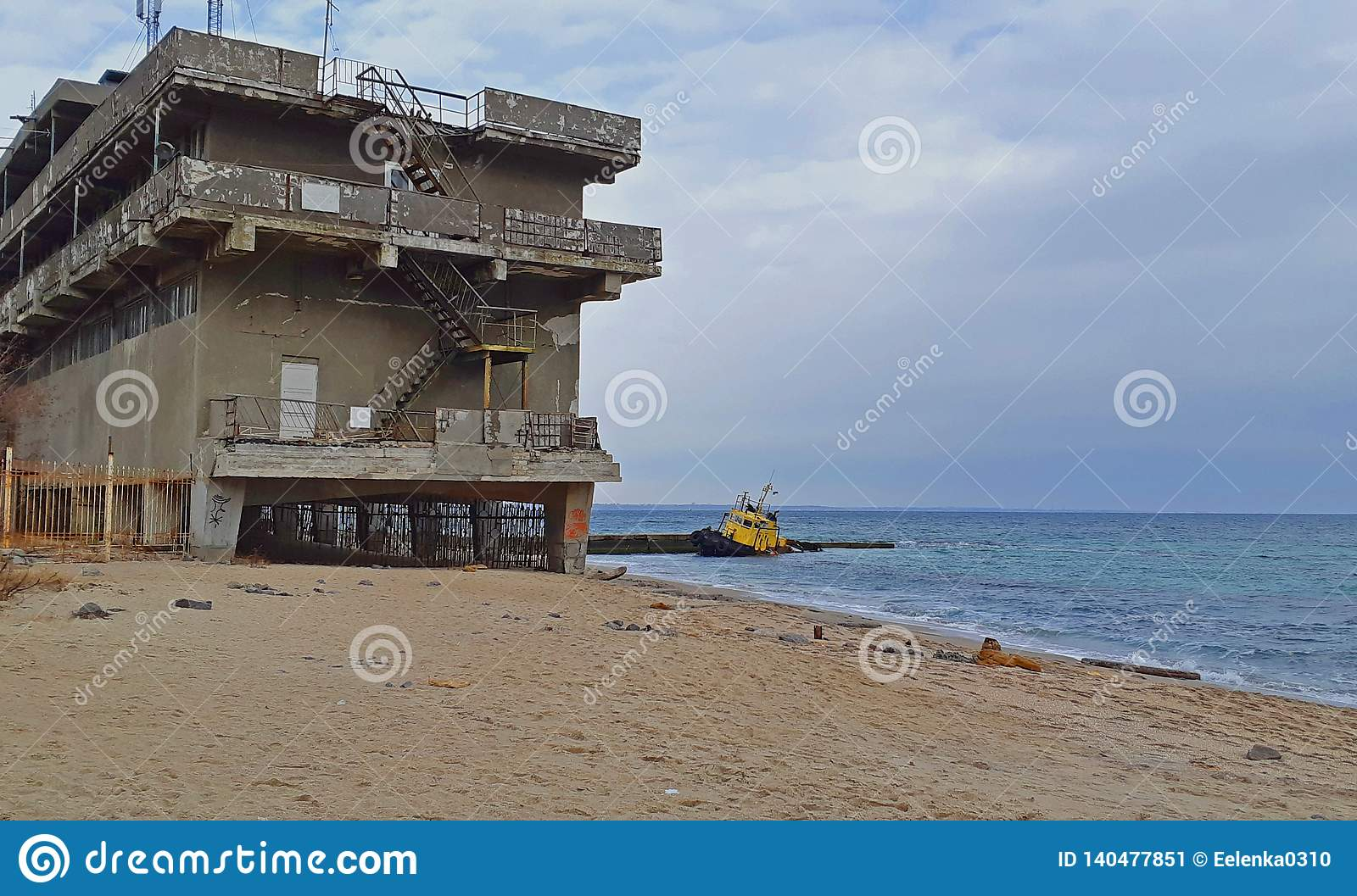 Old flooded towing ship and the abandoned building near the shore.Dramatic view of the flooded boat near the shore.