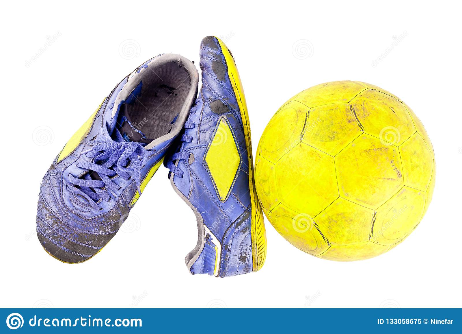 e166ad981f6 Old football shoes damaged and old dirty yellow futsal ball on white  background football object isolated