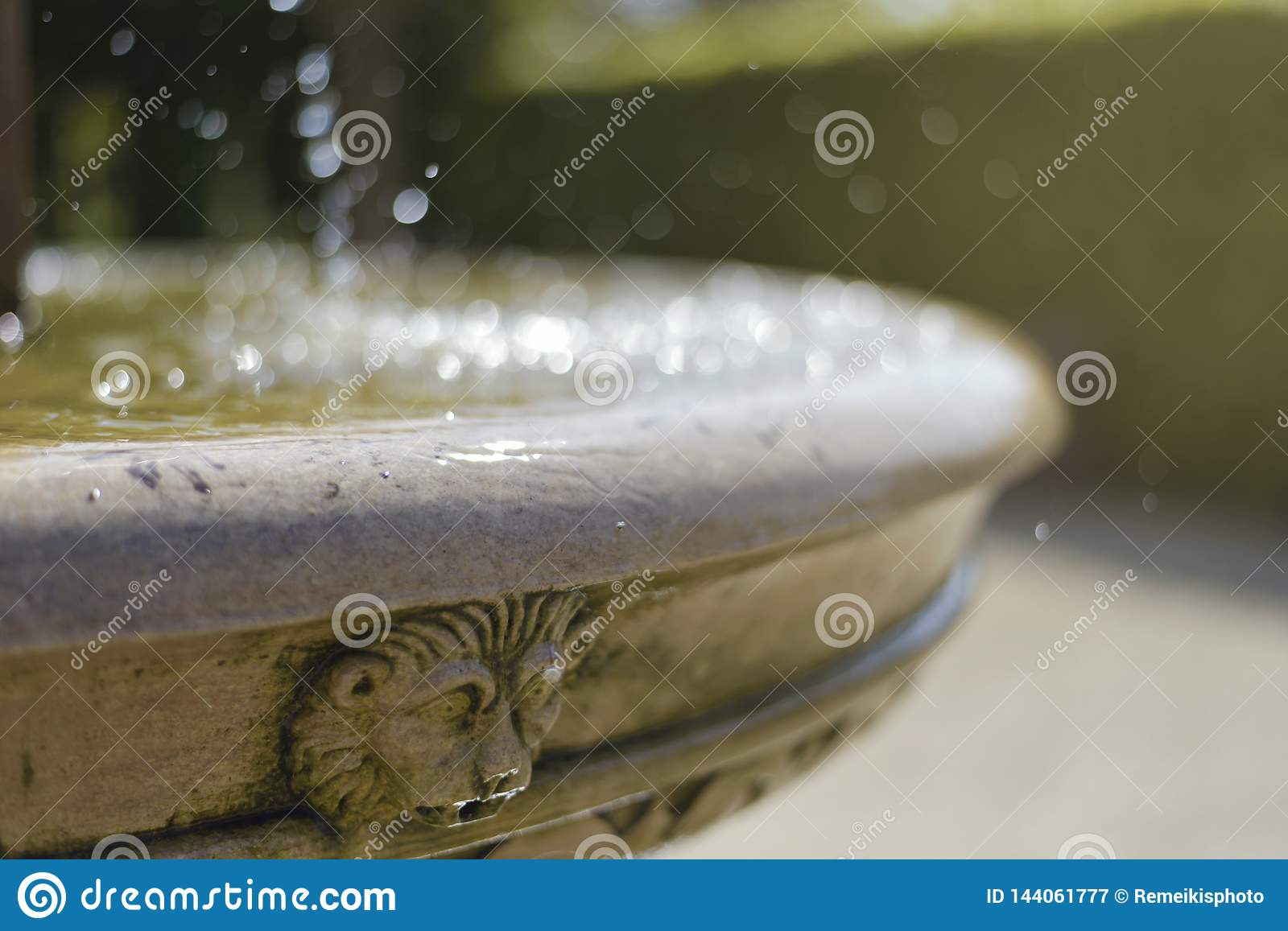 Old fountain with the lion head. Hot summer day. Water splashing