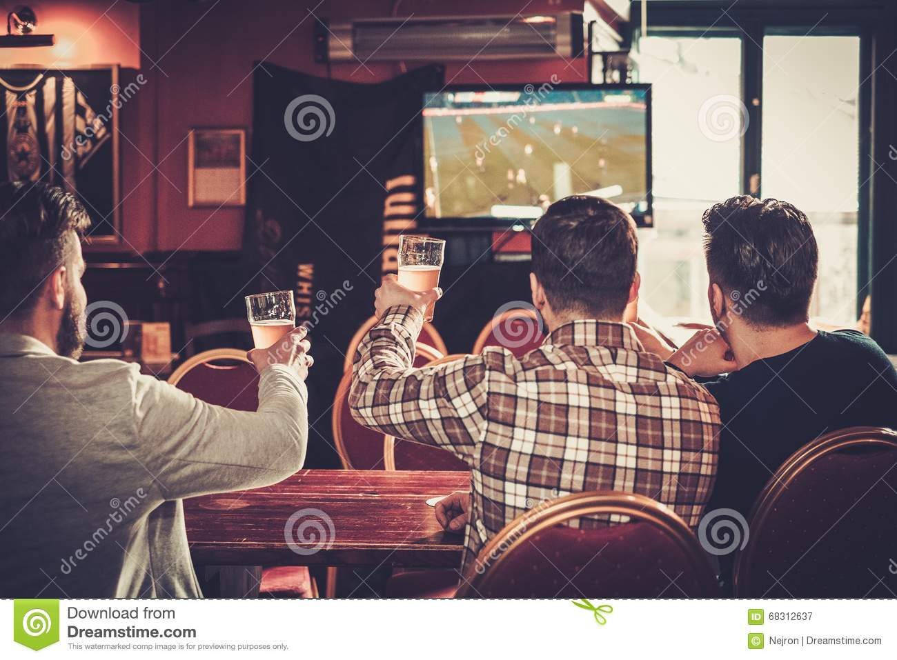 Old friends having fun watching a football game on TV and drinking draft beer at bar counter in pub.