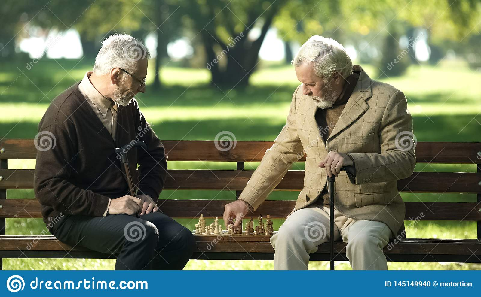 Old friends sitting on bench in park and playing chess, happy leisure time