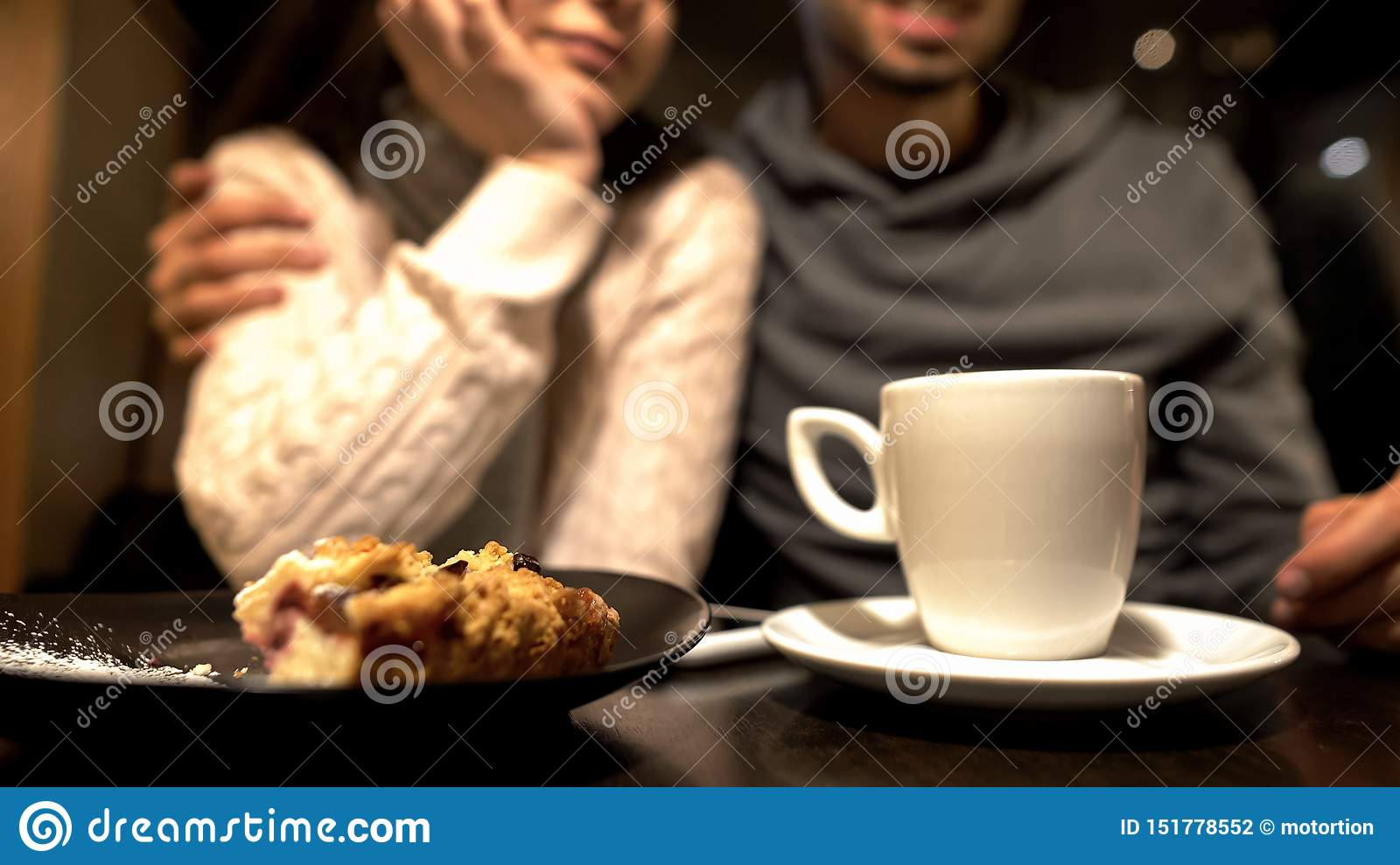 Old friends sitting in cafe, hugging and talking, warm relationship, close up