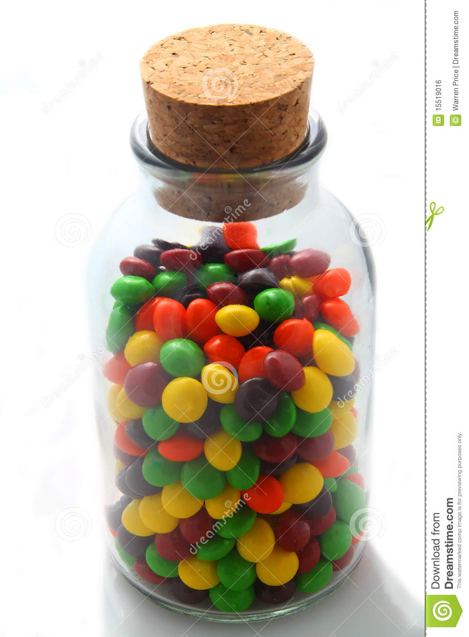 Closeup of various colors of candy in an antique glass jar with cork
