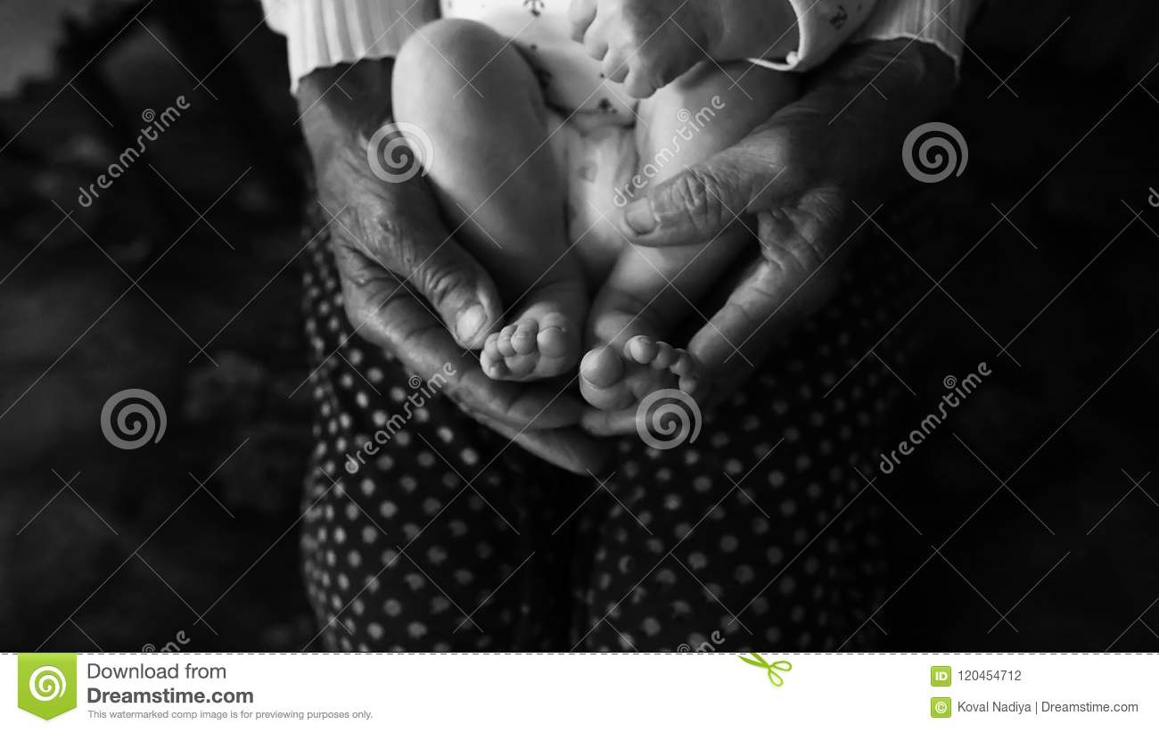 Old grandmother hands holding newborn feet, fourth generation family life. black and white shot, the concept of a family and a new