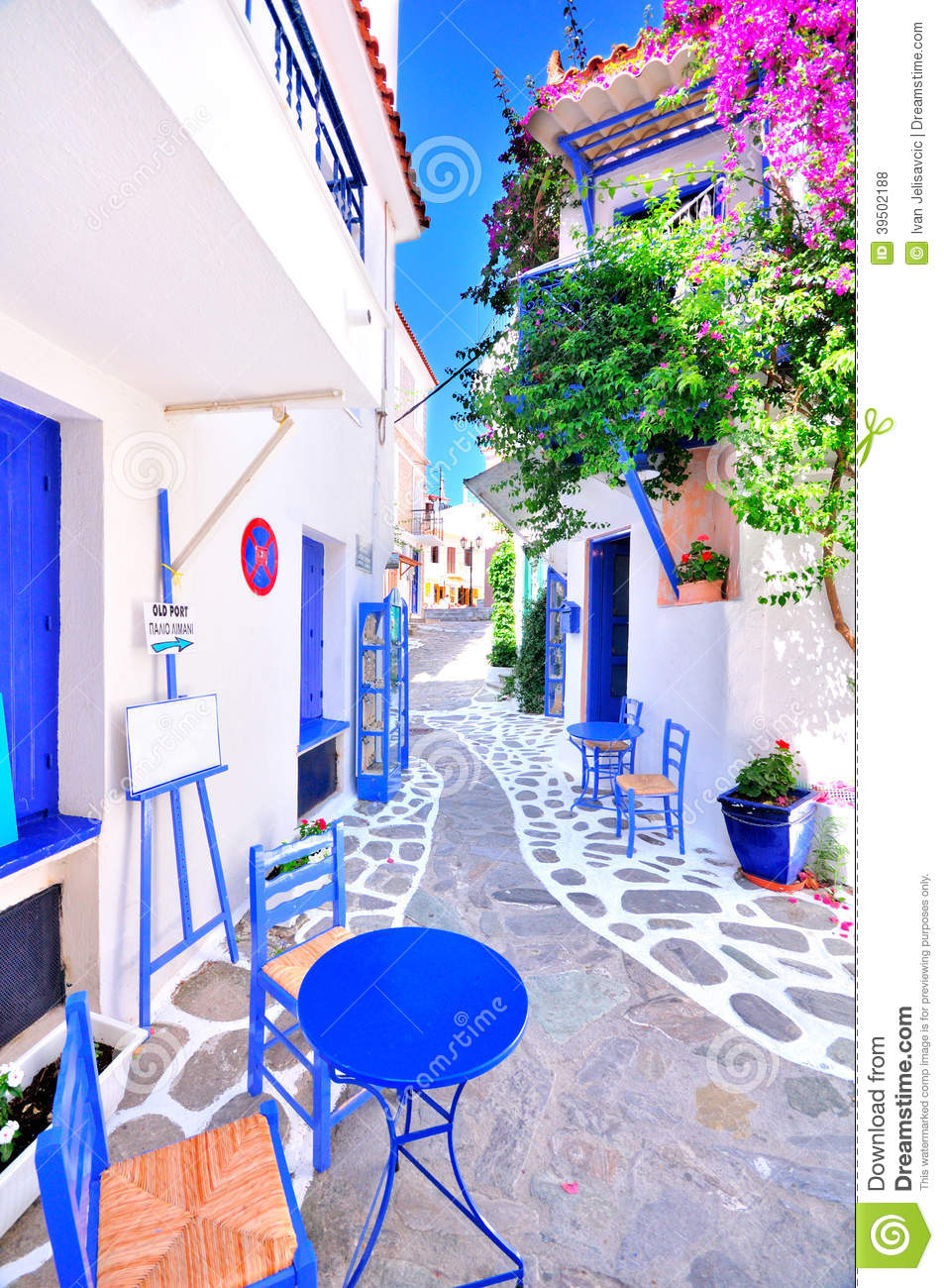 Old greek town, narrow streets, white walls, blue furniture and beautiful bougainvillea