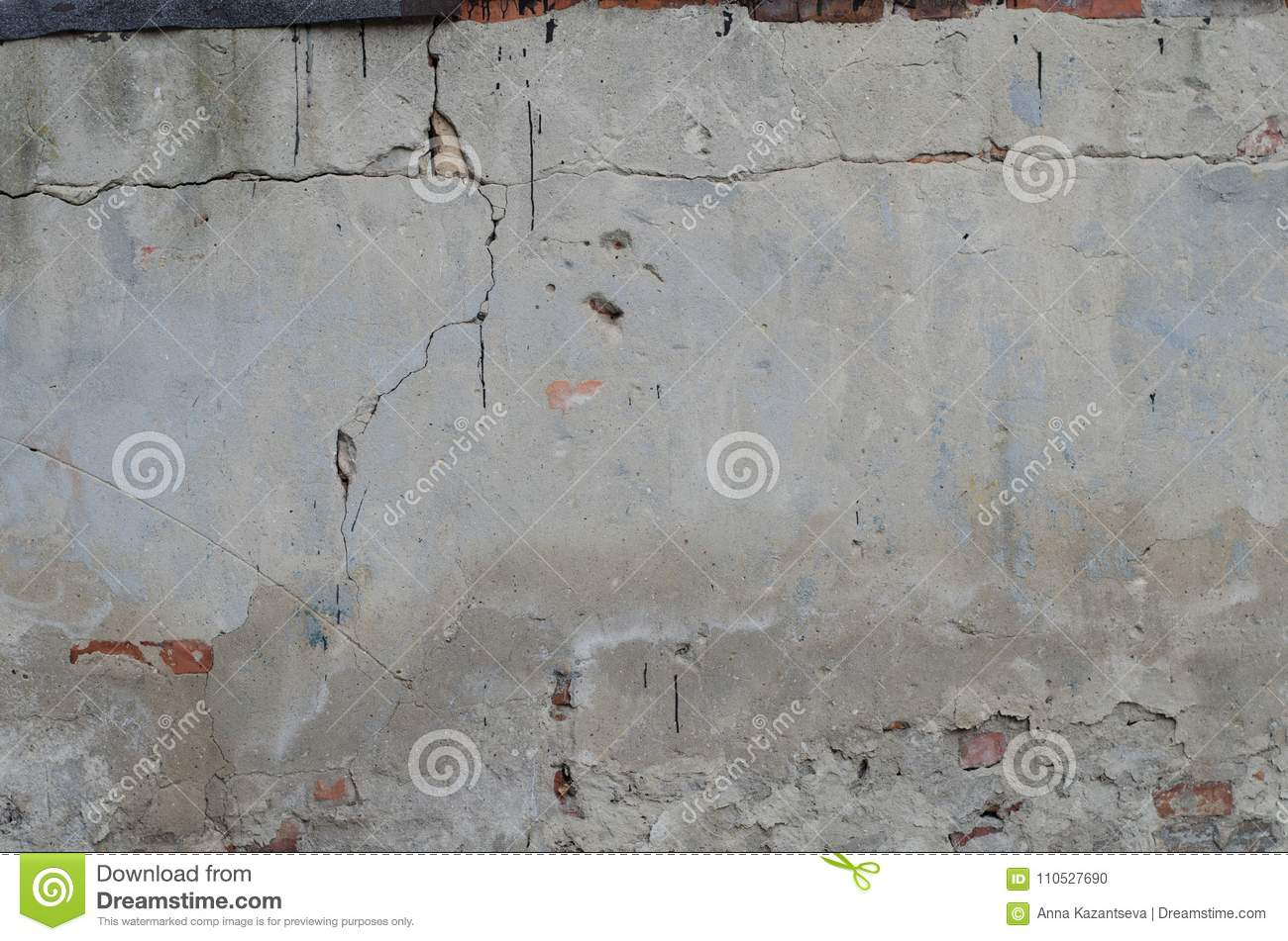 old grey concrete garage wall with red bricks and cracks stock photo
