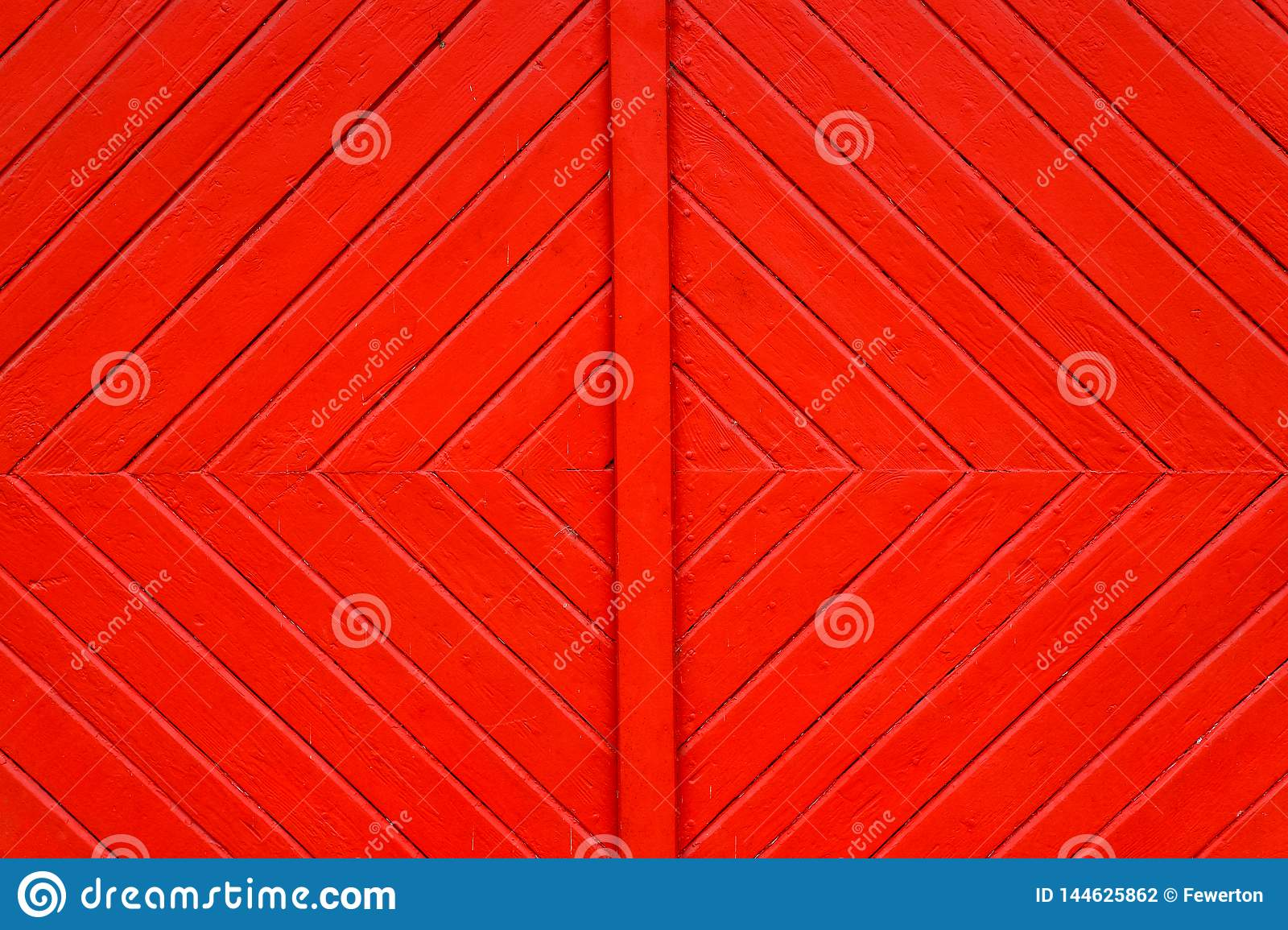 Old grungy and weathered red orange painted wooden wall plank door detail with diagonal lines forming squares as simple saturated