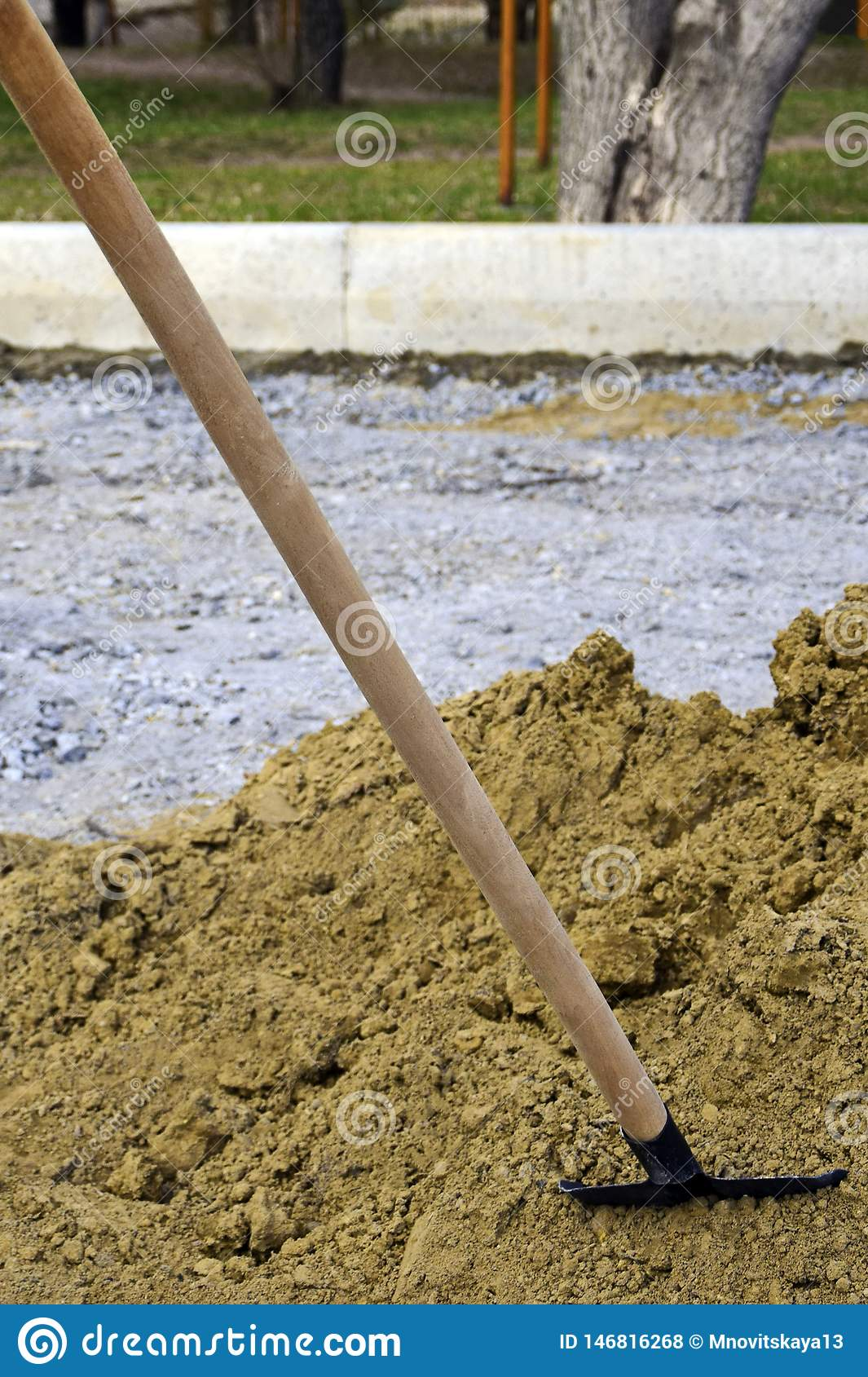 Old hand shovel stuck into a pile of sand at a construction site