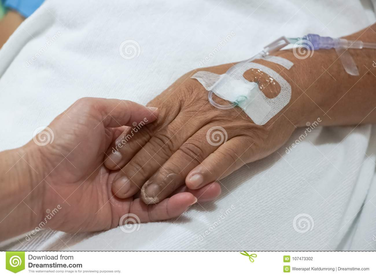 Old hands holding each other with IV solution