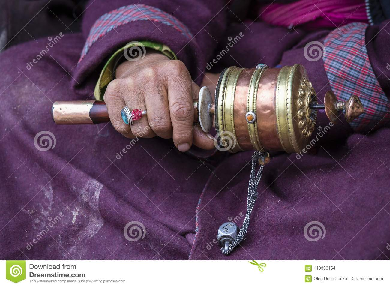 Old hands of a Tibetan woman holding prayer buddhist wheel at a Hemis monastery, Leh district, Ladakh, Jammu and Kashmir, north In