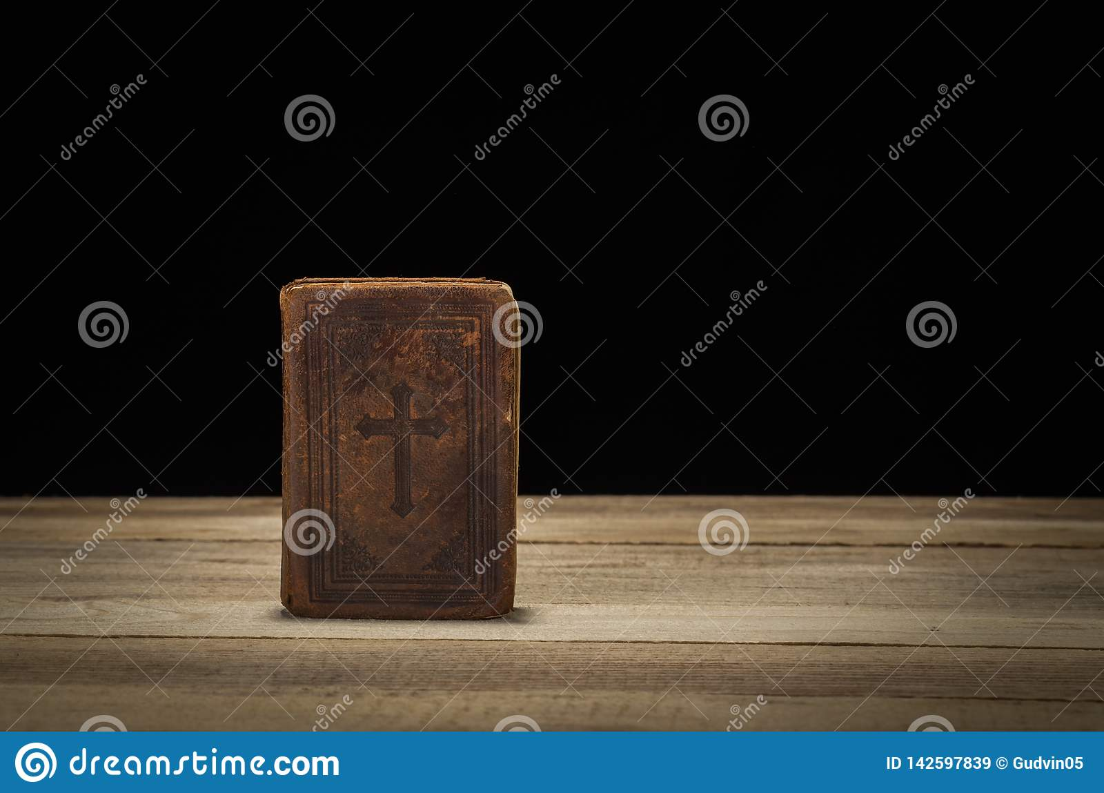 Holy Bible on a wooded table. Black background