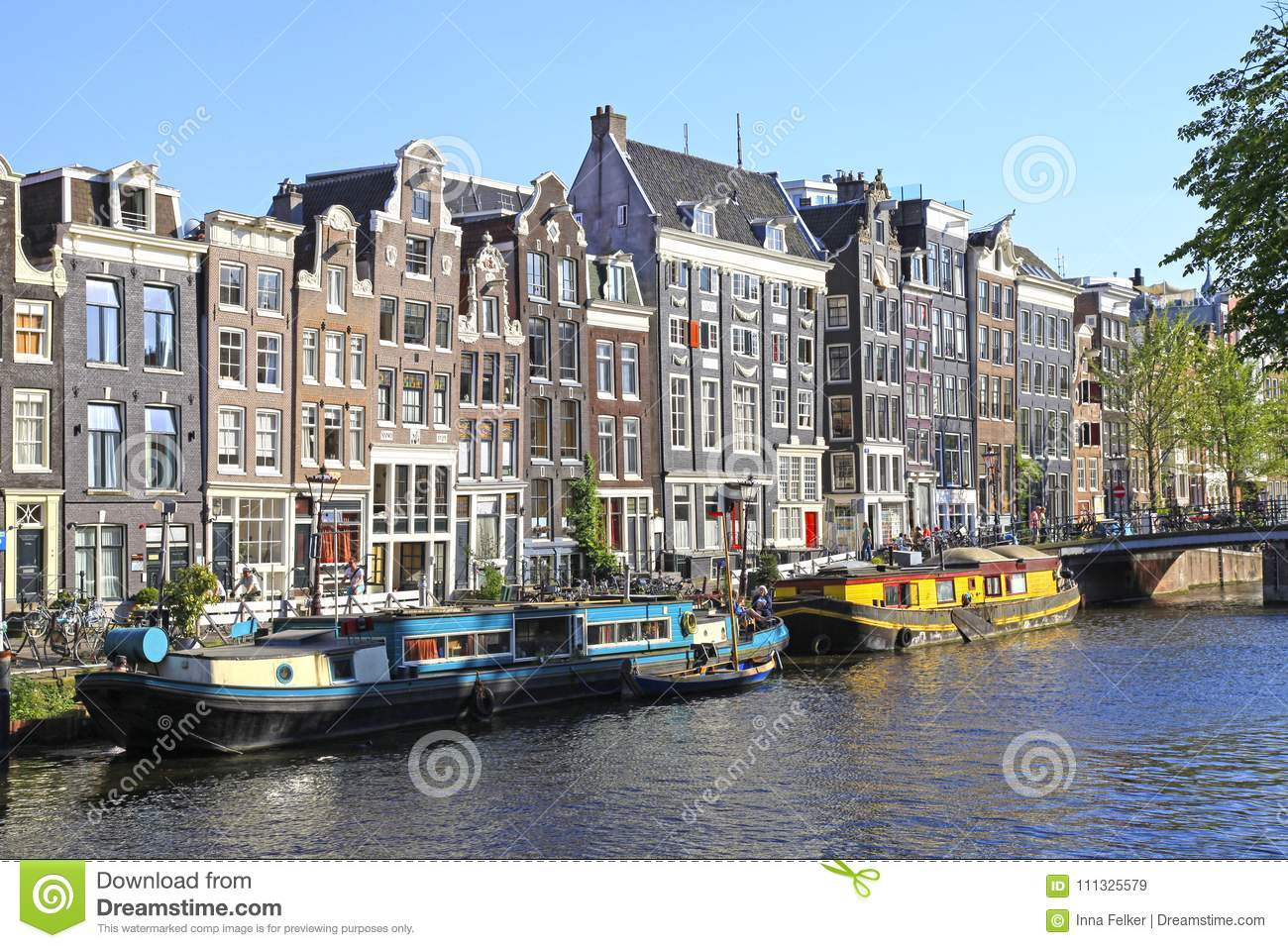 Old houses of traditional architecture and ship along canal,Amsterdam,Netherlands.