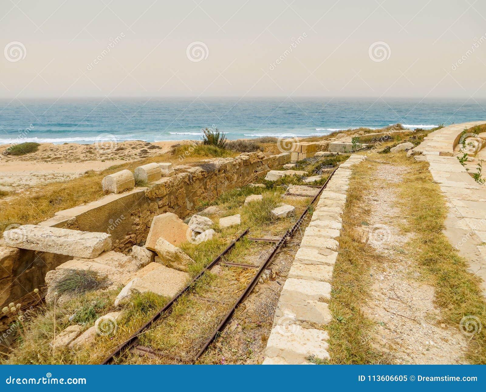 Old Italian railroad tracks among ancient Roman ruins on the Mediterranean coast of Libya at Leptis Magna