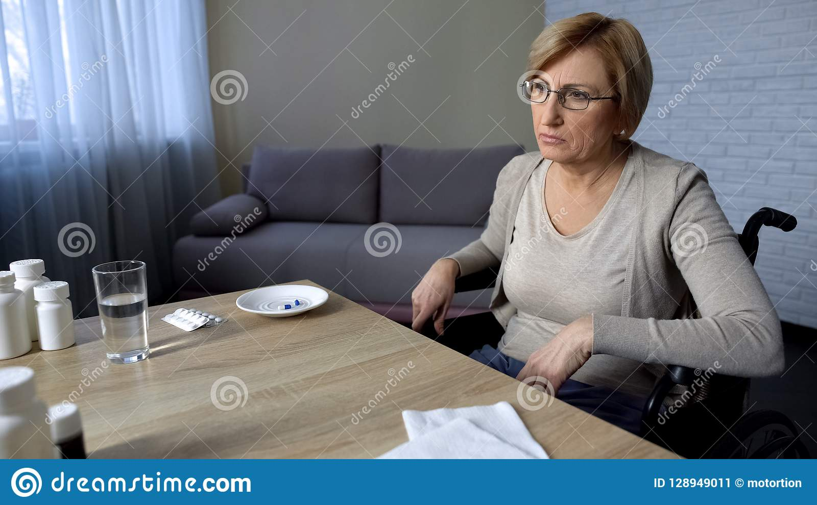 Old Lady Sitting In Wheelchair At Table Feels Lonely And ...