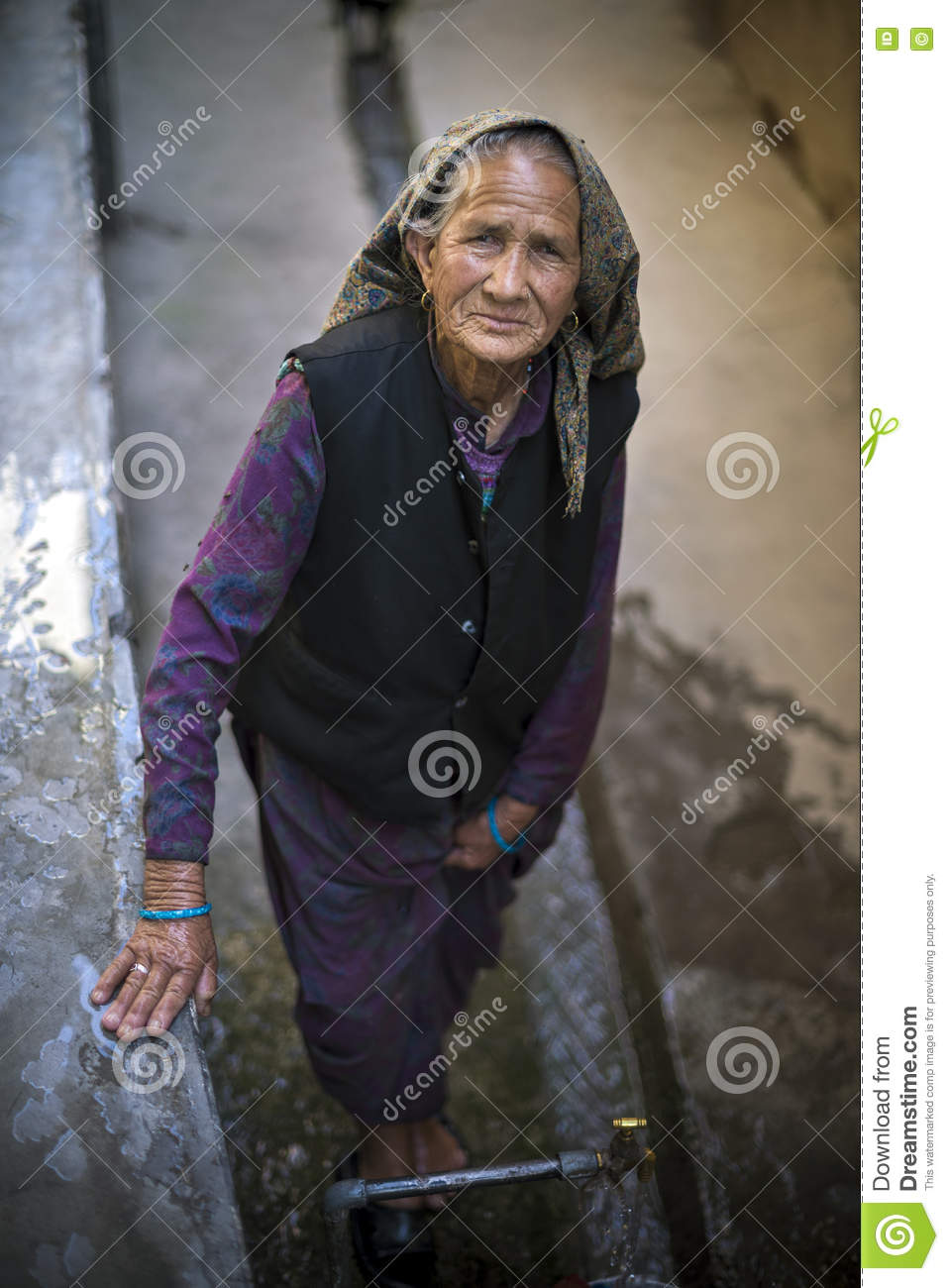 An Old Lady Standing Looking Up With Headdress In