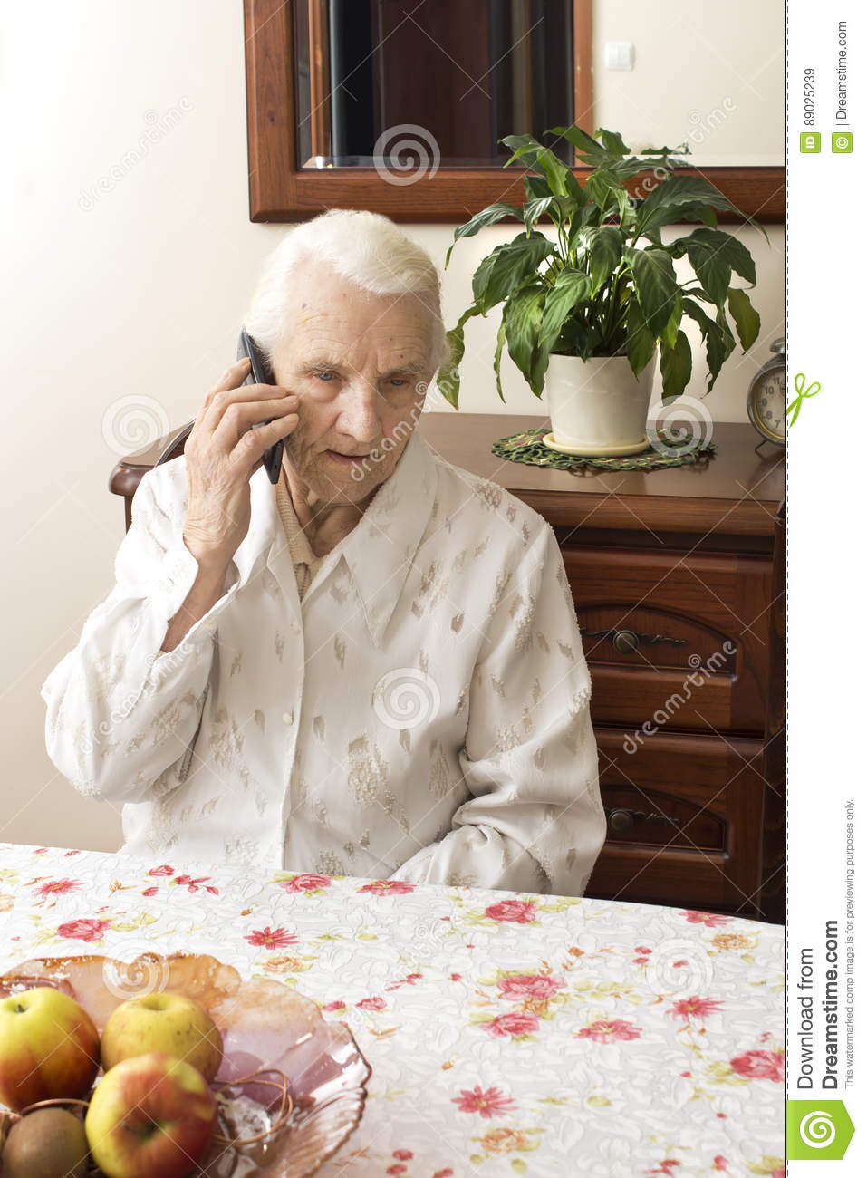 The old lady talking on a cell phone while sitting at a table in the living room.