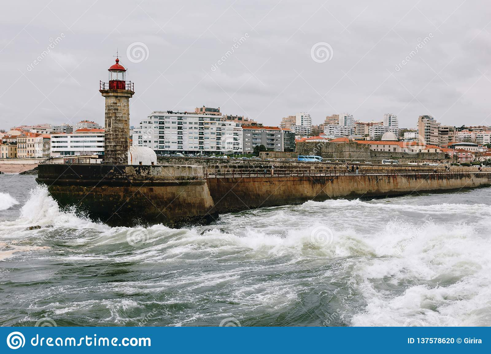 Old lighthouse and granite pier at the mouth of Douro river, Porto