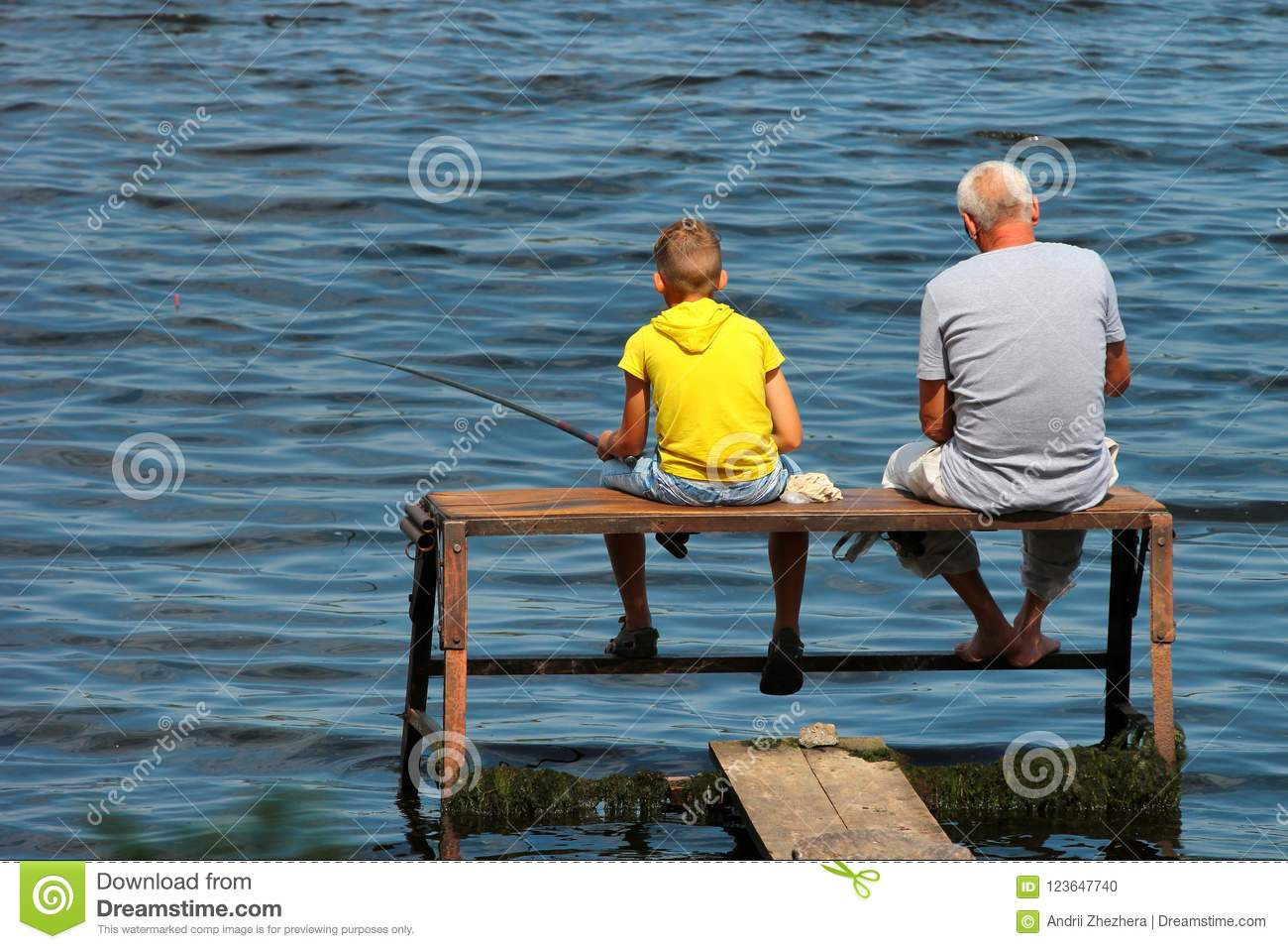Old man and a boy sit on a self-made fishing platform with rods