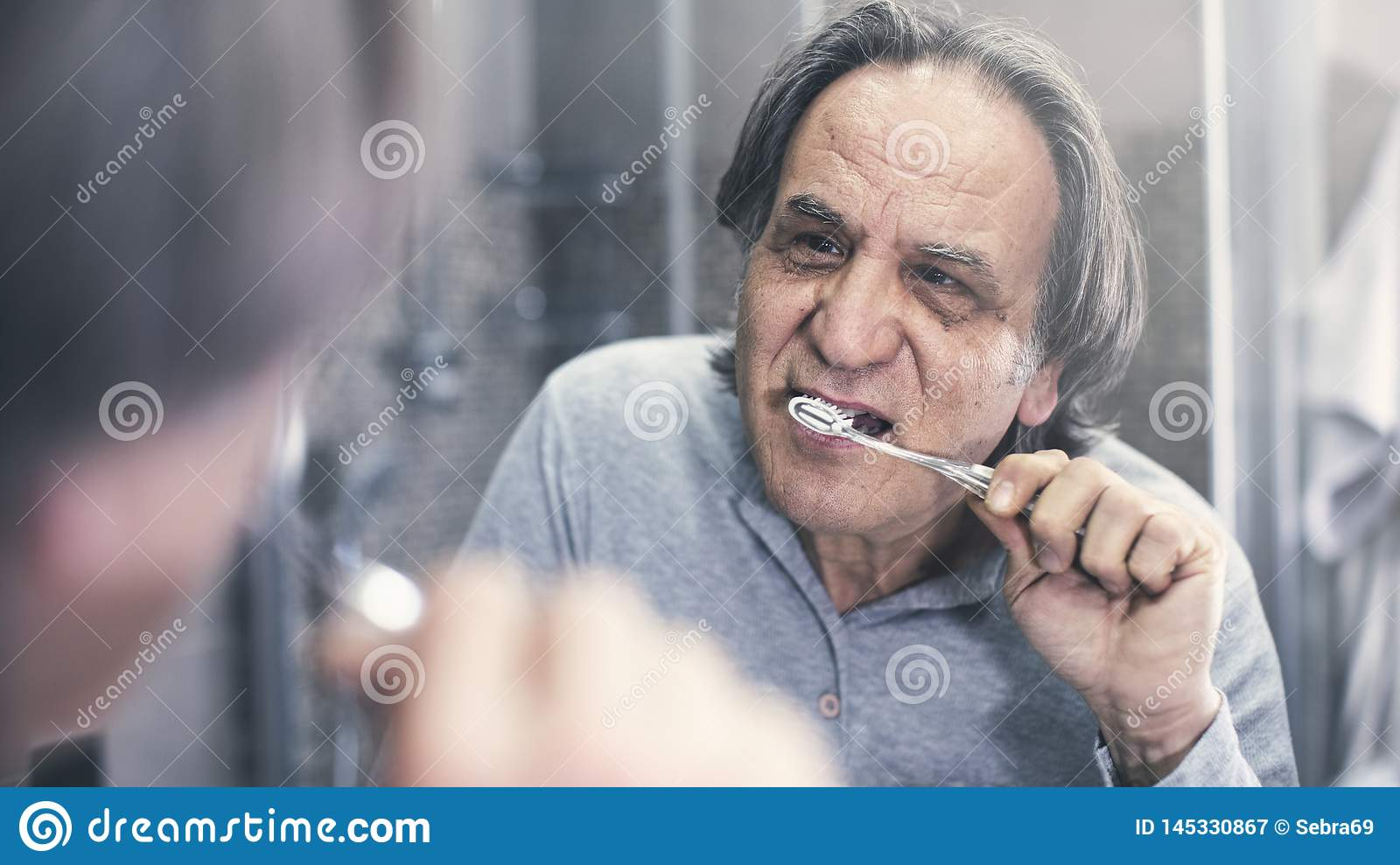 Old man brushing teeth in front of the mirror