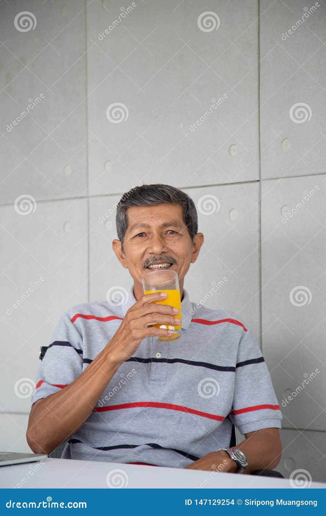 Old man drink orange juice for healthy in his work room