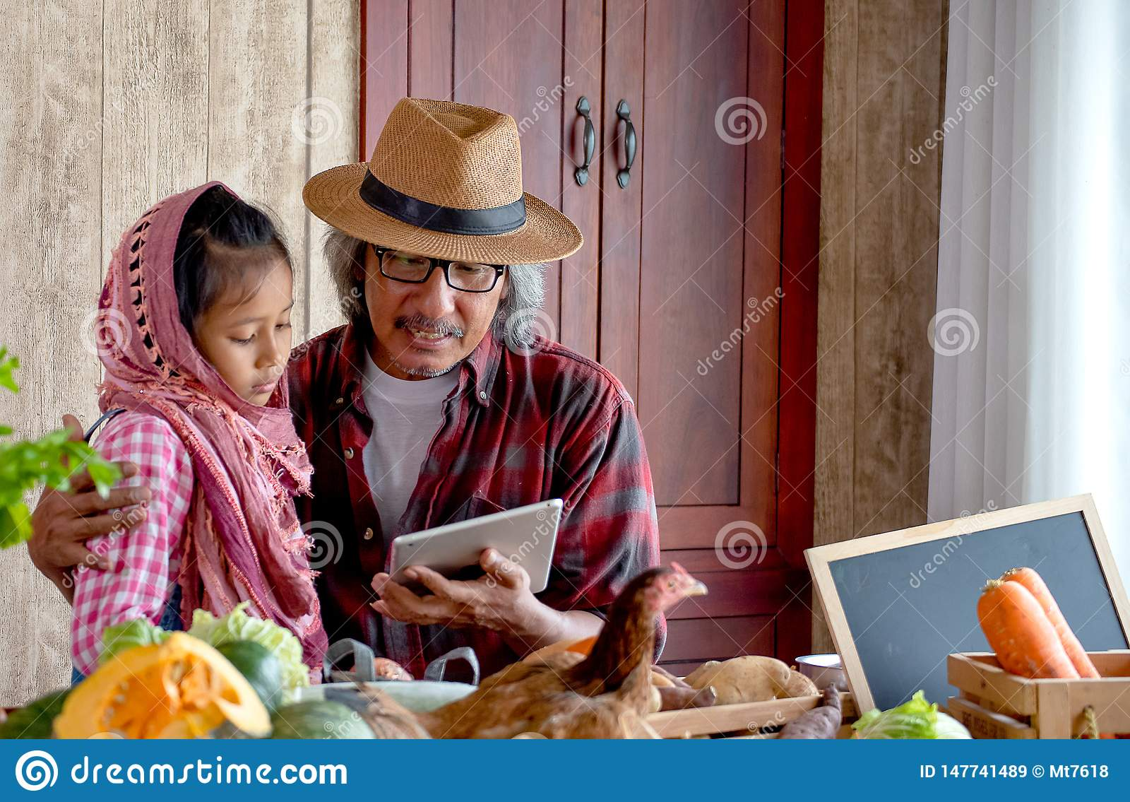 Old man grandfather with hat explain about his menu for cooking to his grandchild by using tablet in the kitchen