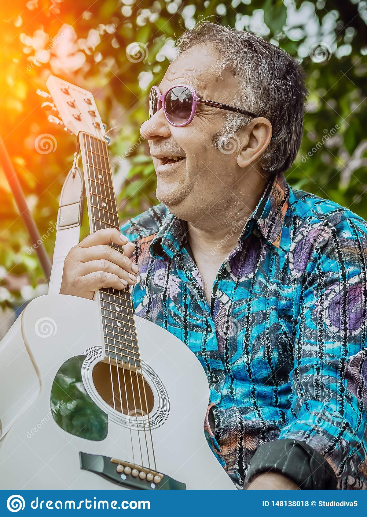 An old man with a guitar enjoys life