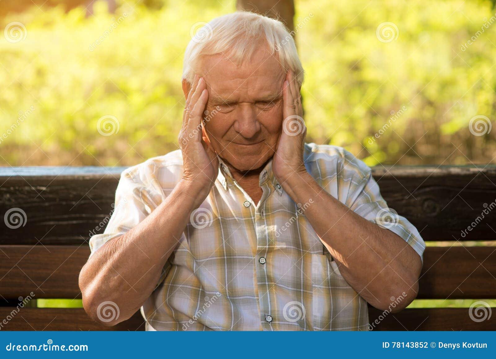 Old man getting head something is