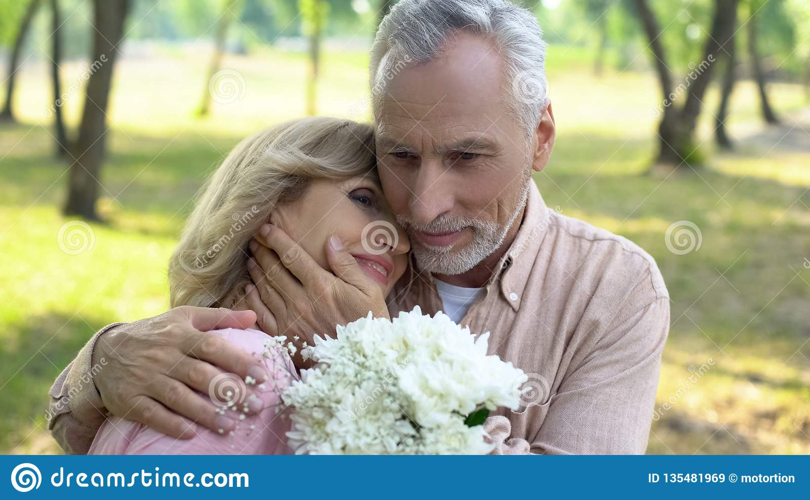 Old man hugging happy wife holding flowers, celebrating marriage anniversary