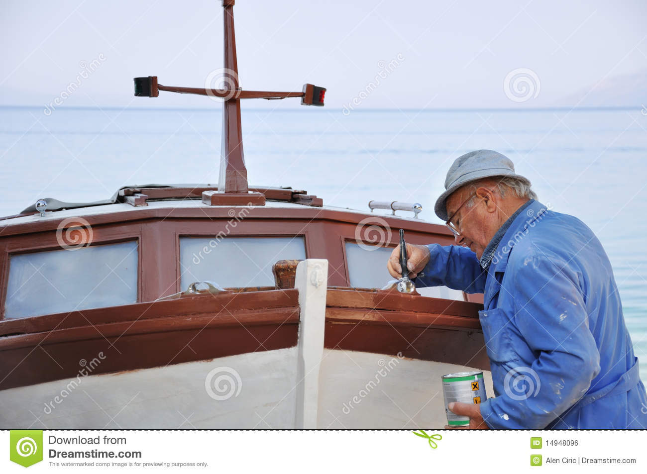 Old man painting boat