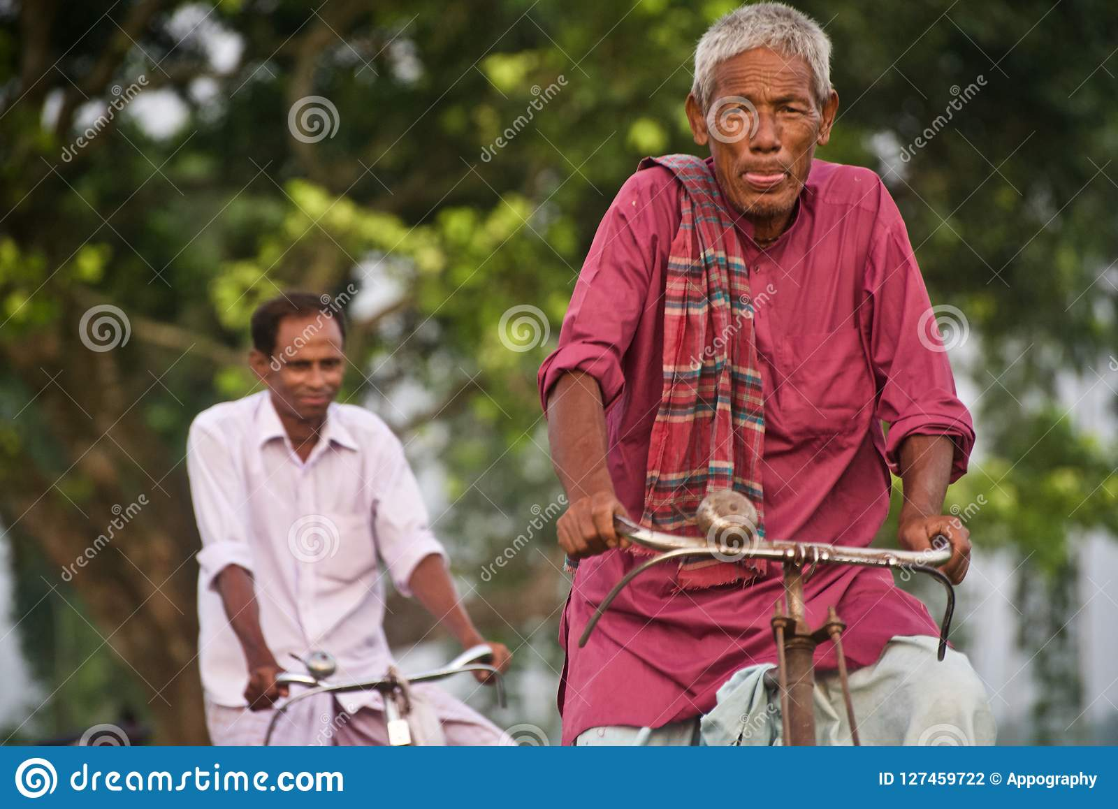 Old man riding a bicycle in a village road unique photo