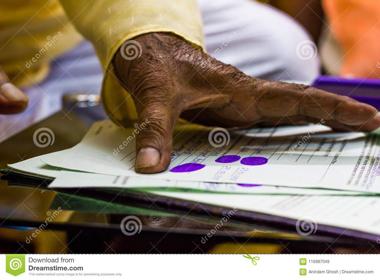 An old man`s hand giving thumb impression on important legal documents.