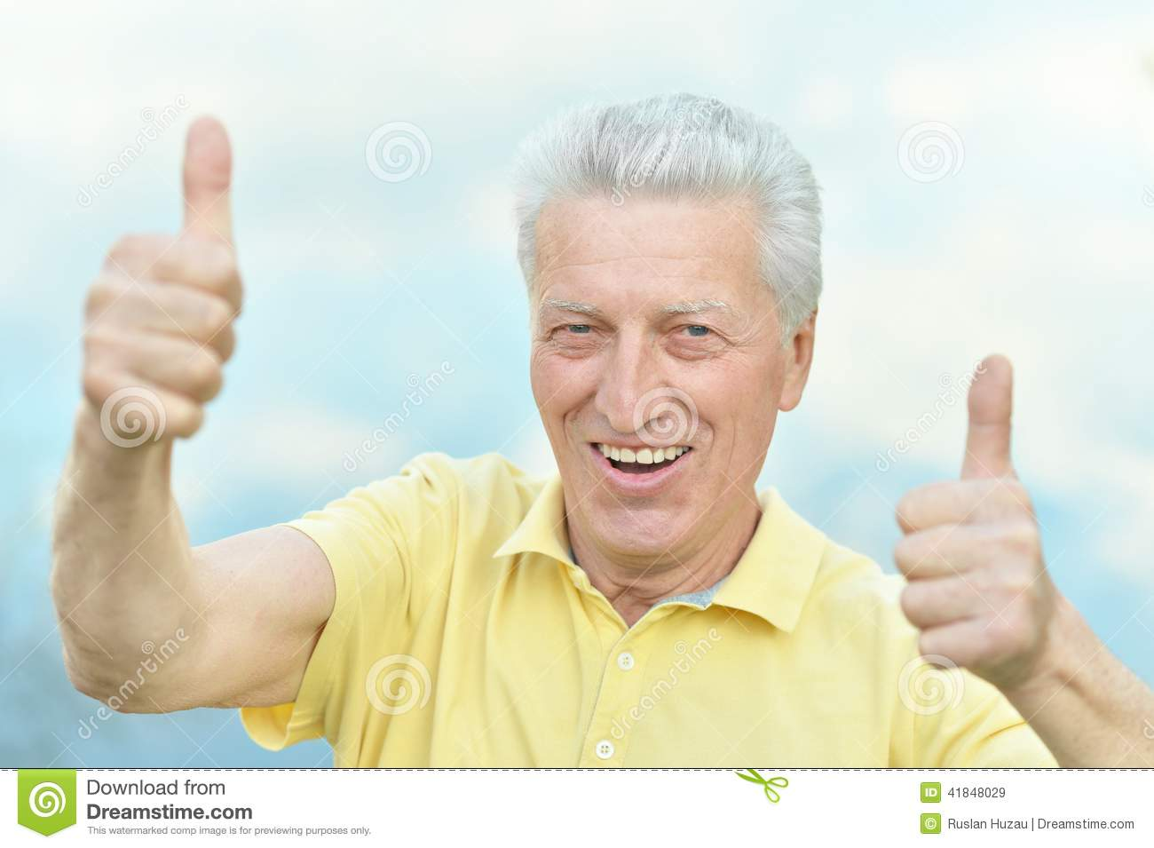Old man showing thumbs up on blue sky background.