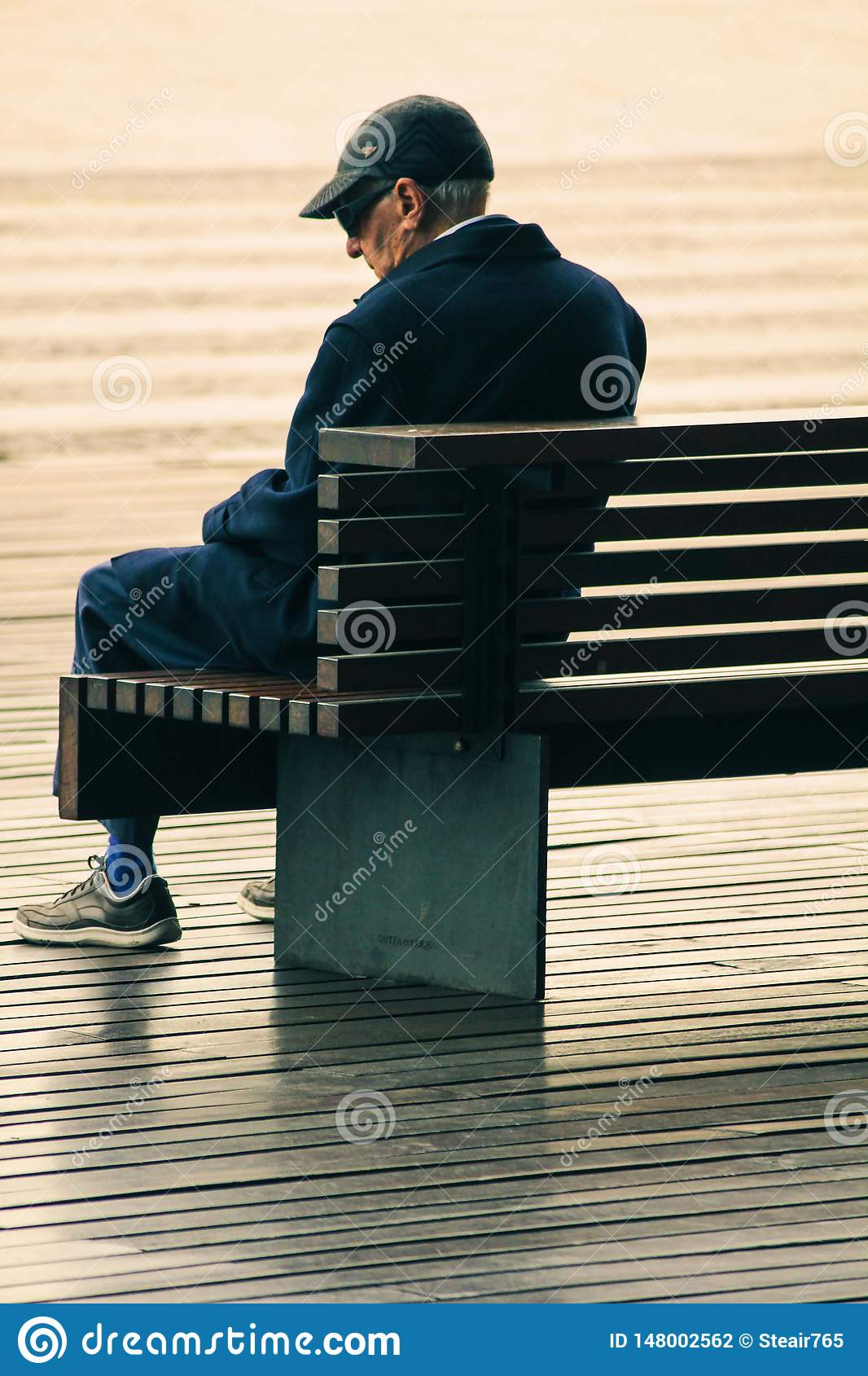 Old man sitting alone on a bench