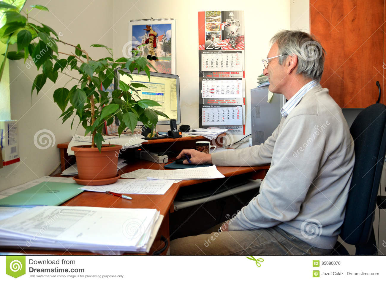 Old Man With Smile, An Accountant, Sit In Office And Works With Computer.