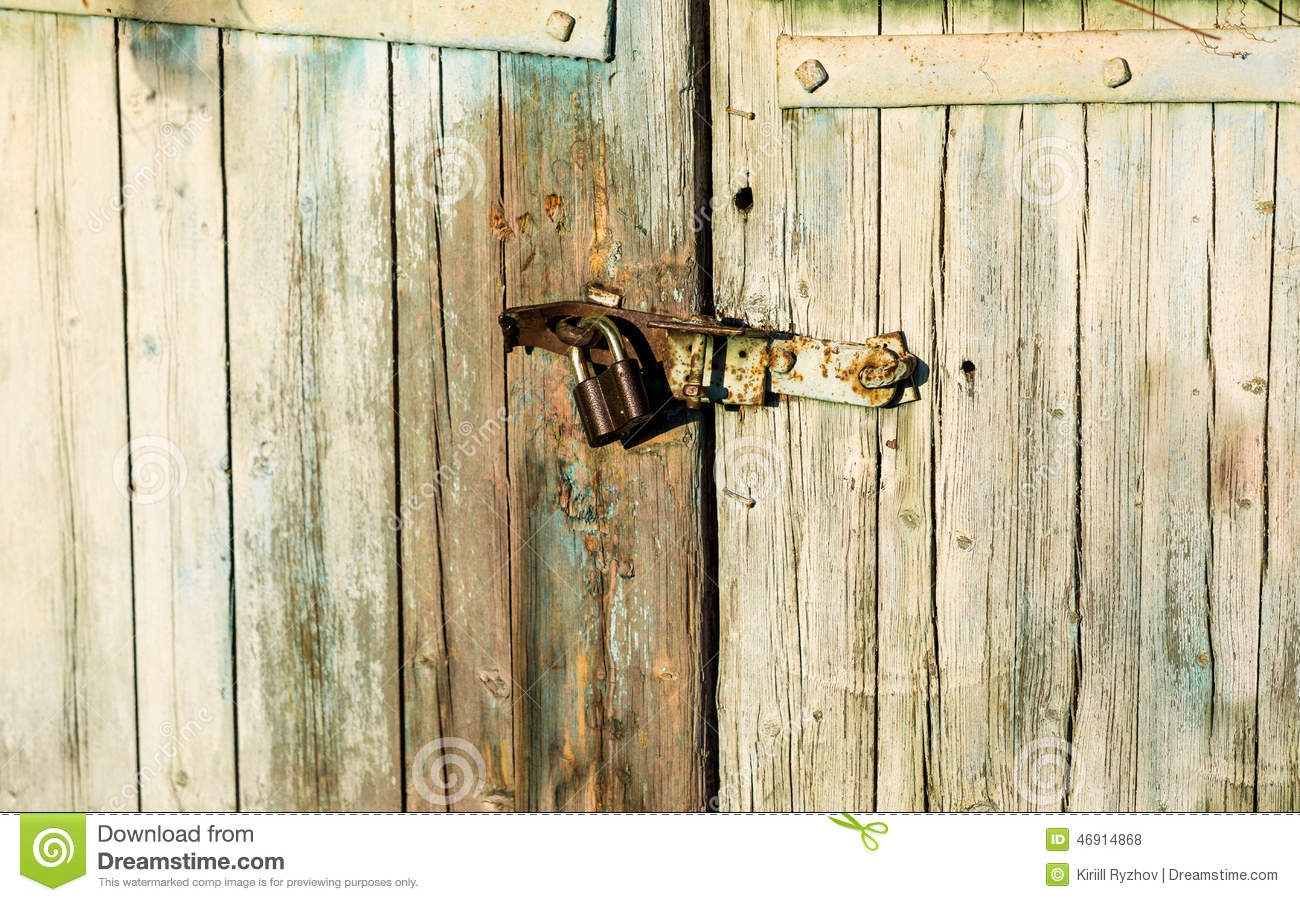 Old Metal Lock Hanging On Wooden Barn Door Stock Photo