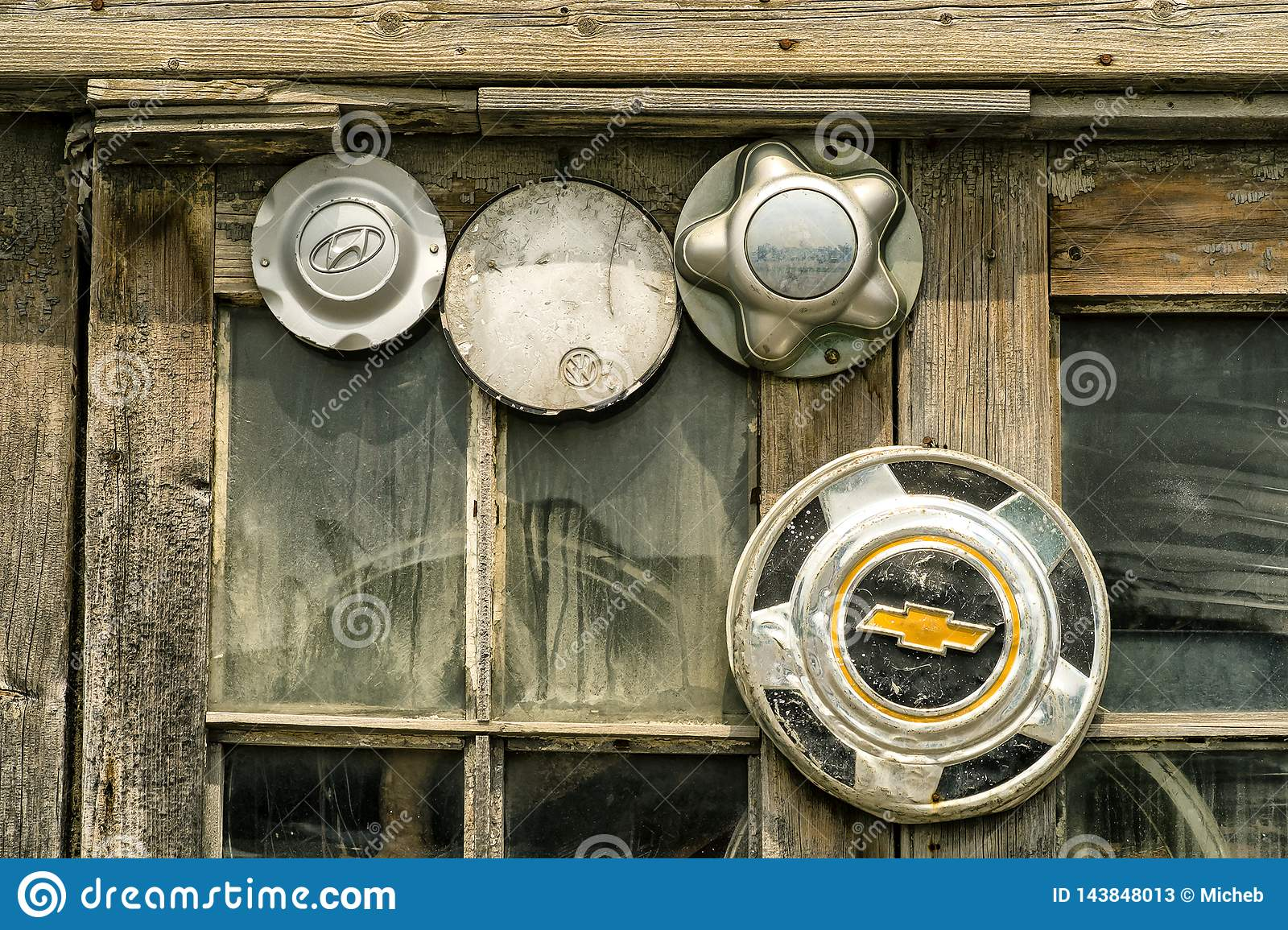 Old mixed hubcaps in a  window