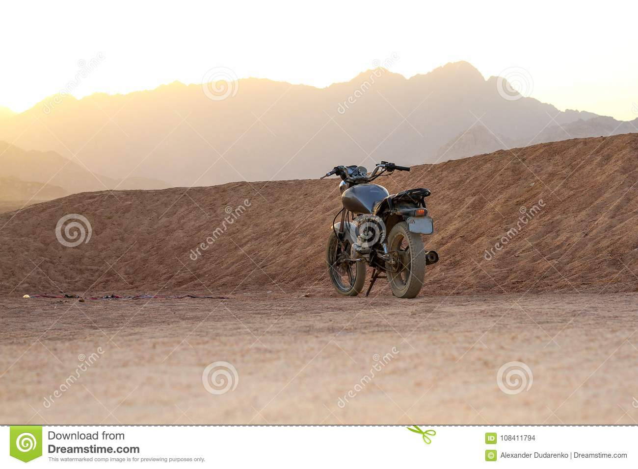 Vintage grey motorcycle in the desert at sunset