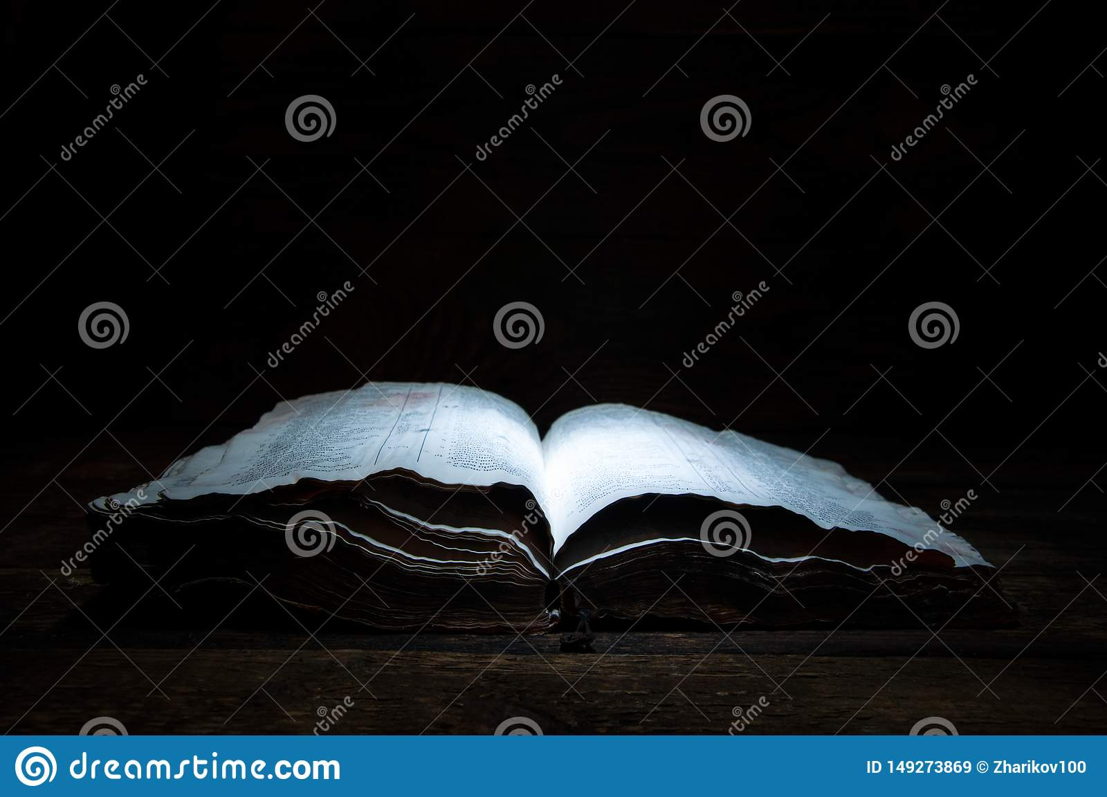 An old open book is lying on a wooden table in the dark. A light shines on the book from above. Holy Bible.