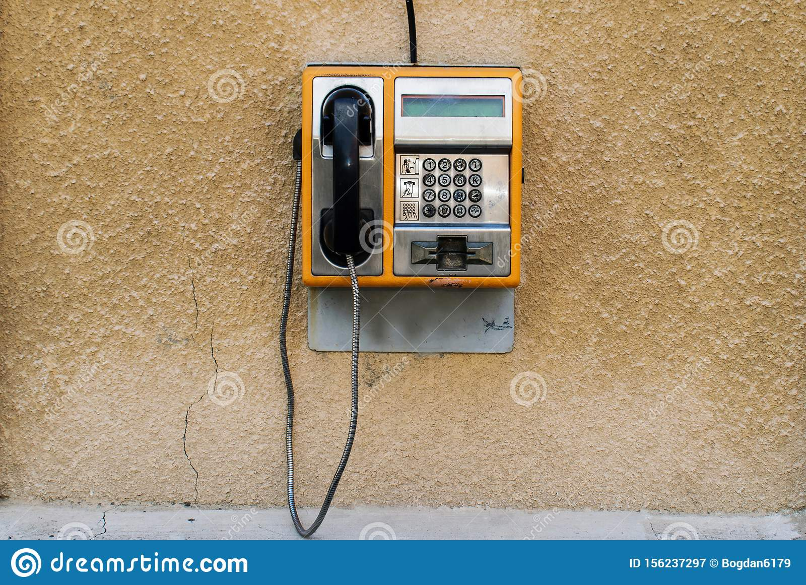An old orange phone with a card. Street phone on a wall. This phone was used in Europe in the 1990s