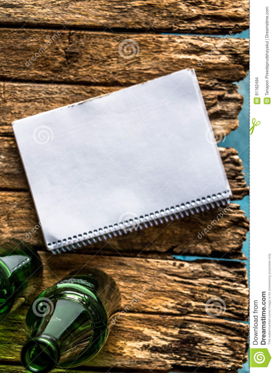 Old paper is placed on the table with a bottle of empty wine pla