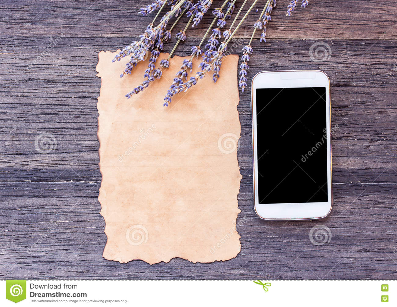 Old paper and smart phone with lavender flower on dark wooden ta