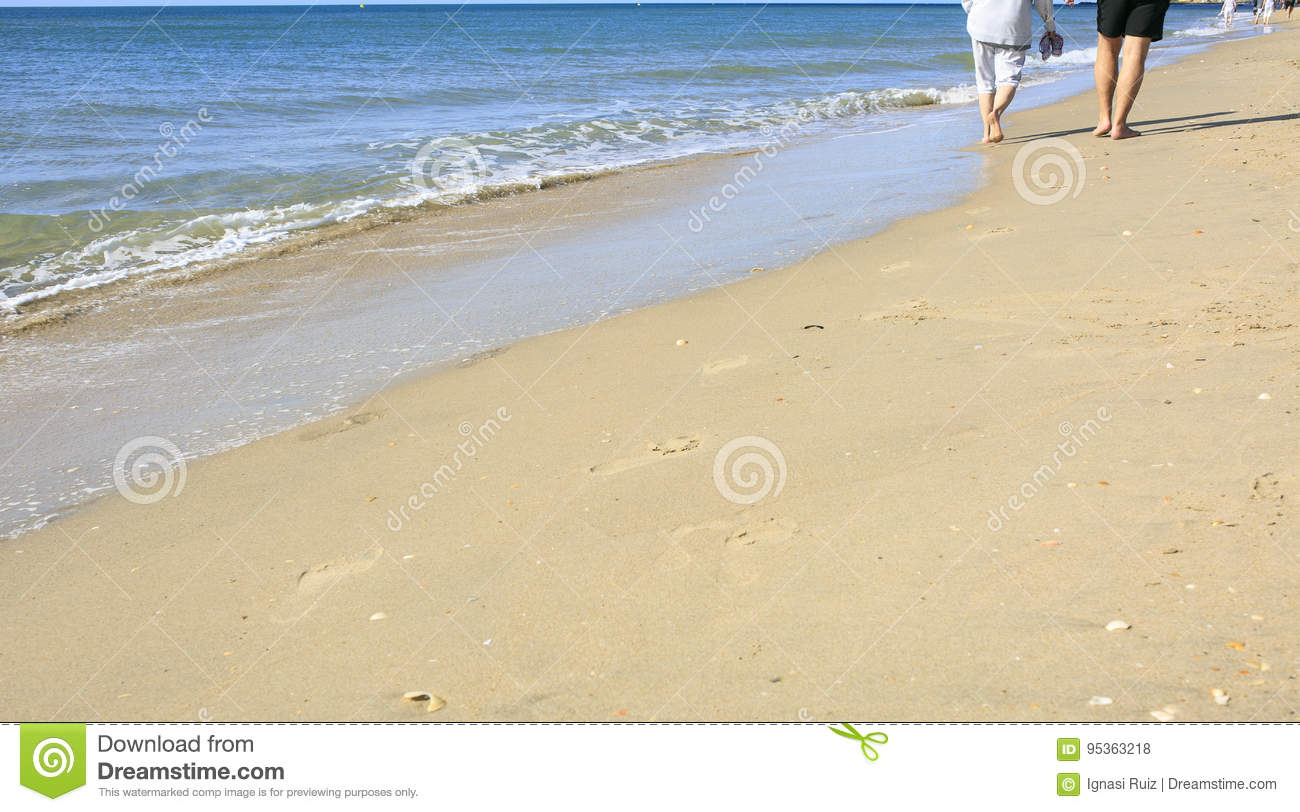 Old people taking a walk on the beach