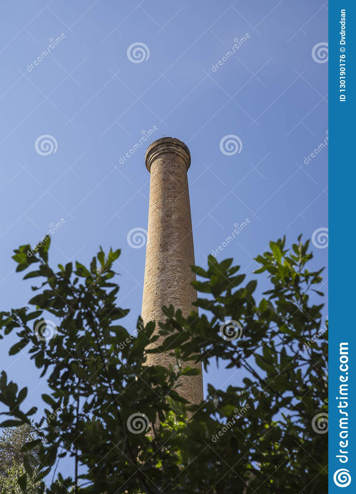 Old red brick chimney of an abandoned factory with blue sky background and trees foreground