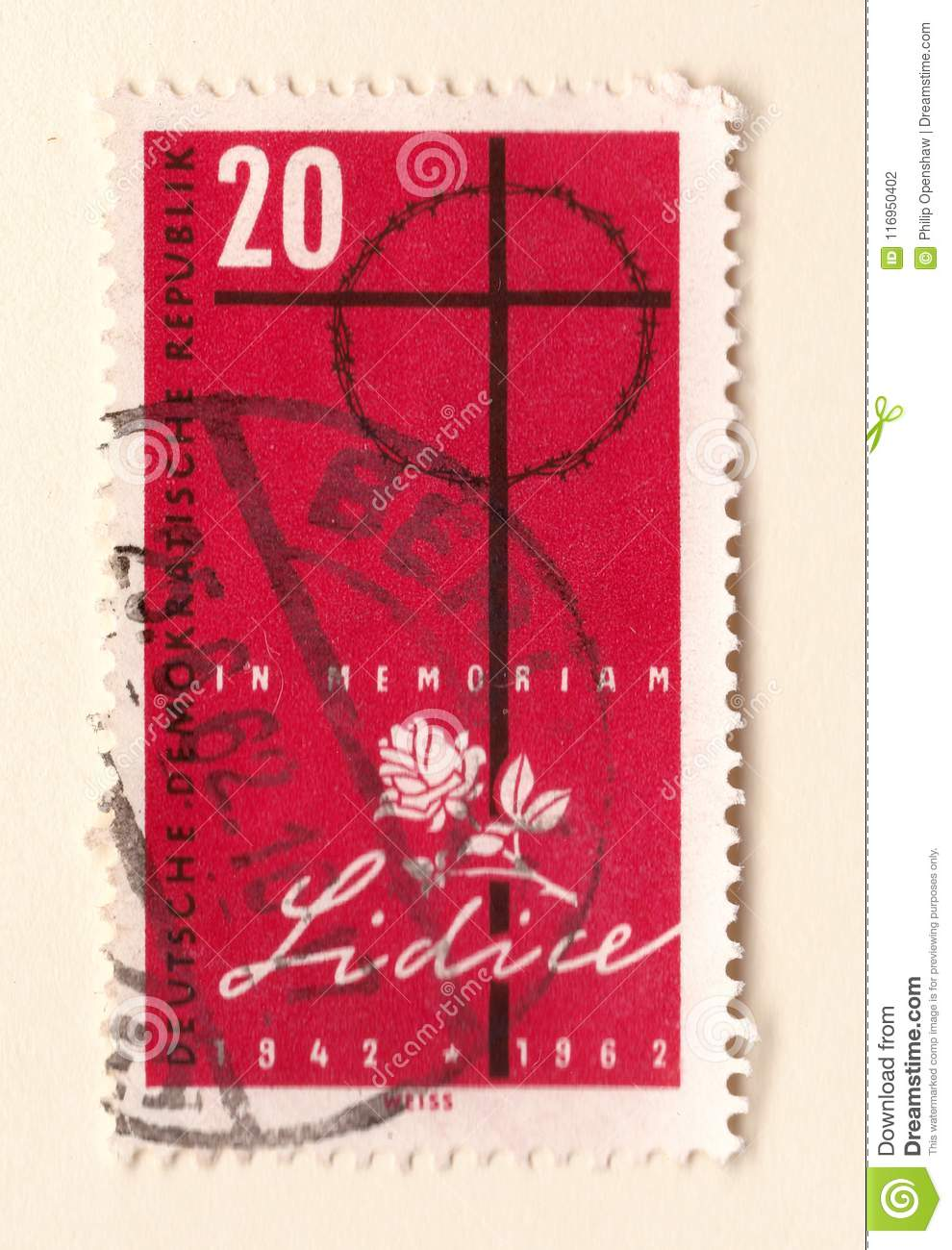 An old red east german stamp commemorating the massacre at lidice with a cross and white rose