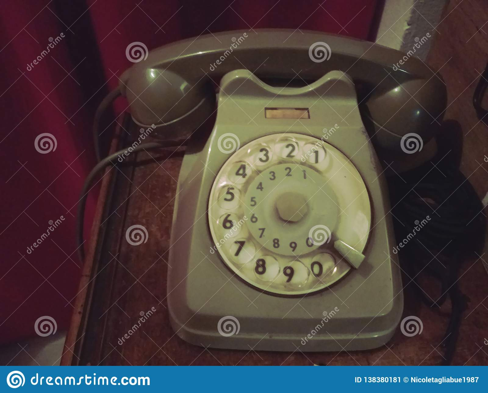 Old retro telephone on a wooden table with red curtain on the background - old photo, vintage style effect