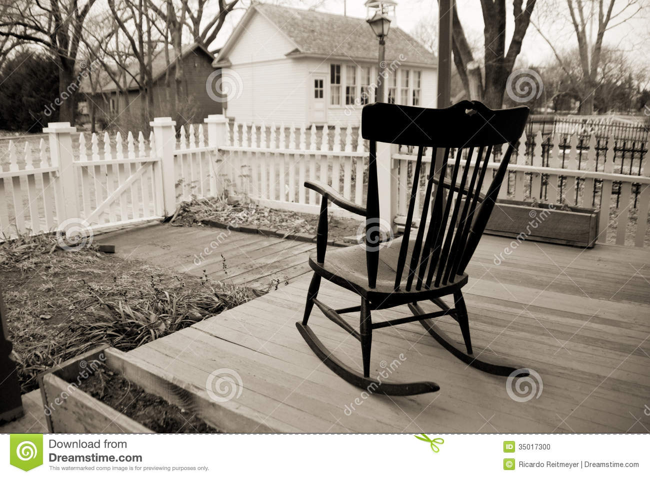 Old Rocking Chair On Wooden Porch With White Picket Fence