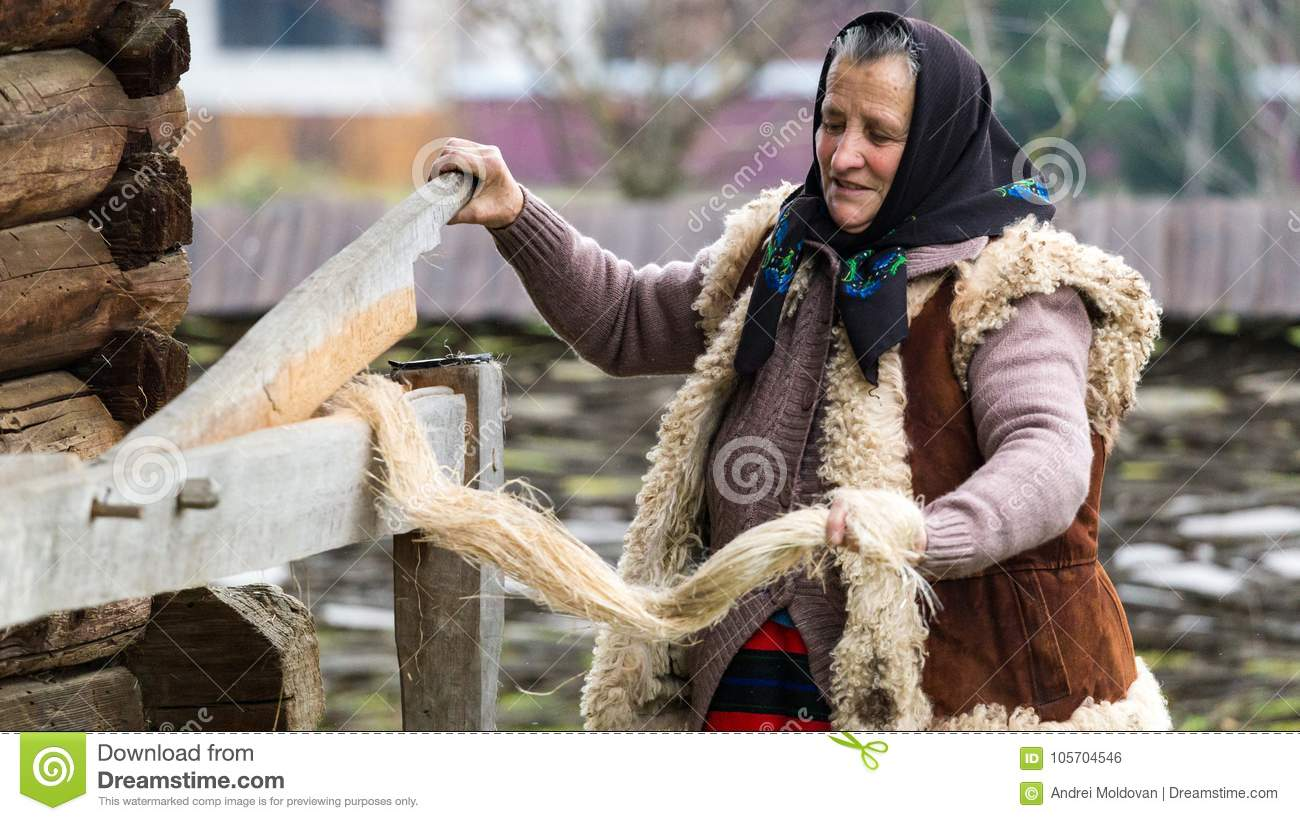 Old Romanian Woman Shows Visitors In A Museum How To Turn Sheep Wool