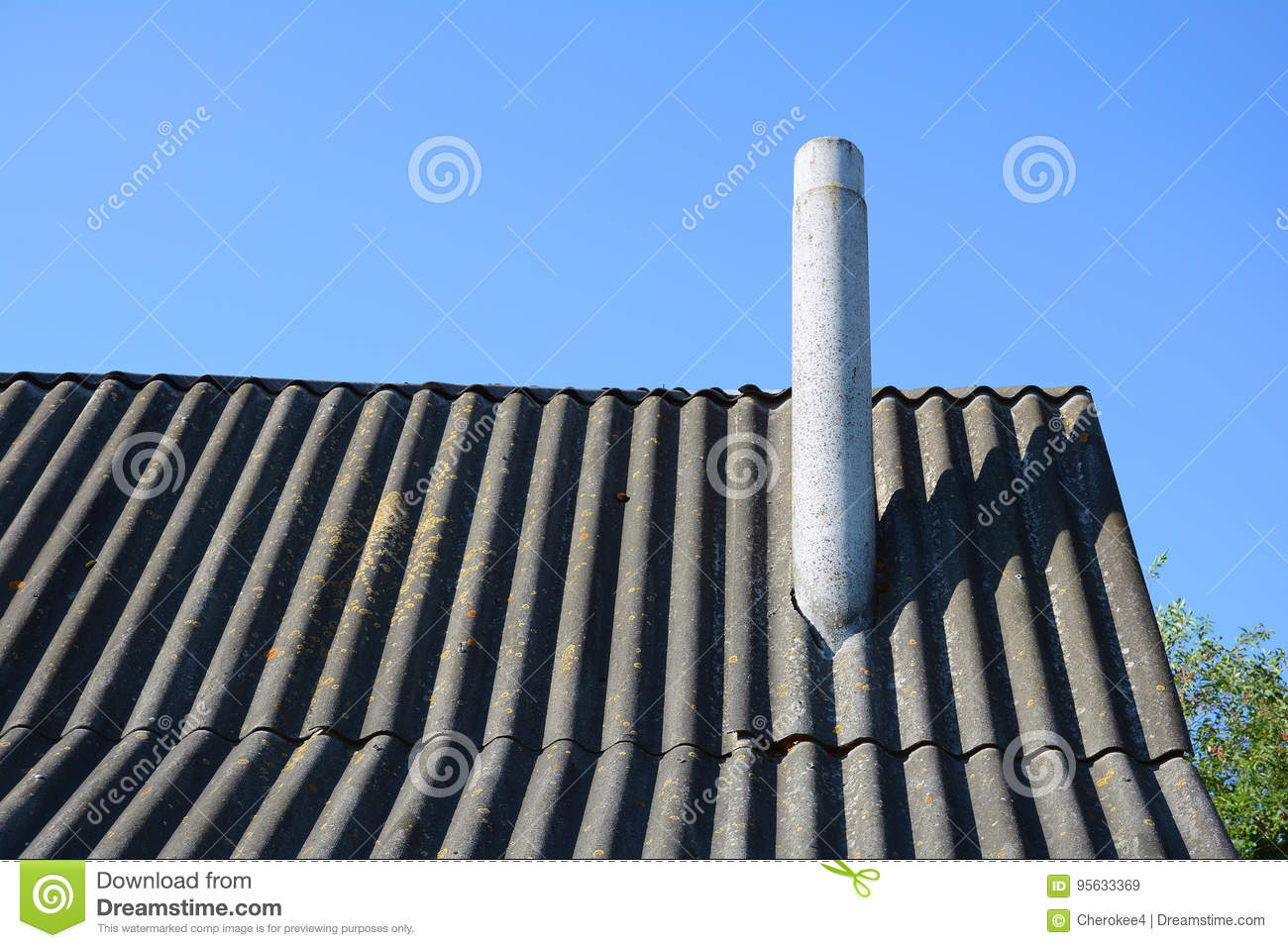 Old roof asbestos roof slates and chimney against blue sky